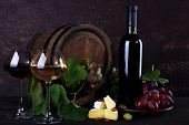 Wine in bottle and in goblets, Camembert cheese, grapes and wooden barrel on wooden table on wooden background