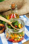 Vegetable salad in glass jar, on  napkin, on wooden background