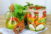 Vegetable salad in glass jars on wooden table, on bright background