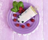 Tasty ice cream pop with fresh berries on plate, on color wooden background