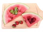 Fresh juicy watermelon slice  with cut out heart shape, filled fresh berries, on cutting board, isolated on white
