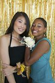 Well-dressed teenager girls hugging at school dance portrait
