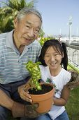 Asian Grandfather and granddaughter gardening (front view portrait)