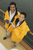 Couple wearing yellow anoraks on yacht (portrait) (elevated view)