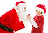 Santa Claus gives a Christmas lollipop to a cute little boy.  Isolated on white.