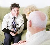 Empathetic couples counselor helping a senior couple with their marriage.