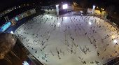 MOSCOW, RUSSIA - NOVEMBER 23, 2013: People skate on the rink with artificial ice in Sokolniki Park in the evening, aerial view. Rink in Sokolniki is widely regarded as one of the biggest in Moscow