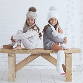 Cute little girls of 5 years old wearing knitted trendy winter clothes posing over white brick wall