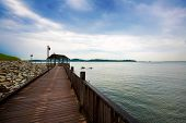 Lovely wooden boardwalk by the sea with clear blue sky