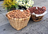 Walnut and chestnut in baskets on paving stone