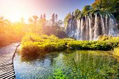 stock photo of morning  - Majestic view on waterfall with turquoise water and sunny beams in Plitvice Lakes National Park - JPG