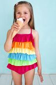 Portrait of 5 years old kid girl eating tasty ice cream over blue