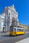 Lisbon, Portugal. August 31, 2014: Tthe iconic yellow tram in front of the Triumphal Arch that connects the Augusta Street and the Praca do Comercio Square