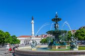 Lisbon, Portugal. August 31, 2014: Dom Pedro IV Square, better known as Rossio with the Dom Pedro IV monument, the Dona Maria II National Theatre in background and one of the two fountains