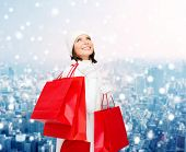happiness, winter holidays, christmas and people concept - smiling young woman in white hat and mittens with red shopping bags over snowy city background