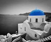 Oia town on Santorini island, Greece. Black and white styled with blue dome of traditional church over the Caldera, Aegean sea