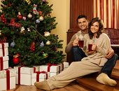 Couple with cups of hot drink near Christmas tree