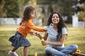 foto of blowing  - Mother and daughter blowing bubbles outdoors - JPG