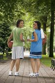 Rear view portrait of two teenage girls with basketballs