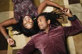 African American couple laying on floor holding hands