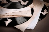 Vinyl records with old paper and butterflies, close-up