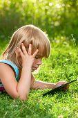 Little girl usng a touch pad in a summer garden