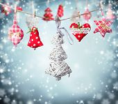 Hand made cloth decoration hanging on rope. Blur abstract snowy background