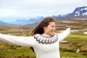 Happy free woman on Iceland in Icelandic sweater. Portrait of girl happy smiling outdoors in nature wearing Icelandic sweater. Pretty Asian Caucasian multiracial female model