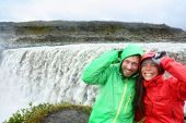 Travel couple fun in raincoats by Dettifoss waterfall on Iceland. People visiting famous tourist attractions and landmarks on Diamond Circle.