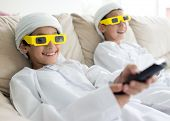Arabic kids having fun wearing 3D movie glasses and watching cinema tv at home on couch