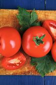 raw vegetables : raw ripe tomatoes ready to prepare on cutting board over blue table