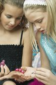 Young girl applying nail polish to friends fingernails poster