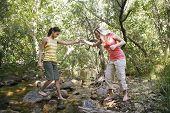 Two teenage girls (16-17) years crossing stream holding hands