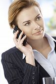 Closeup portrait of attractive businesswoman talking on mobilephone, smiling, looking away.