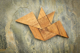 stock photo of tangram  - abstract picture of a flying bat built from seven tangram wooden pieces over a slate rock background - JPG