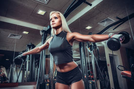 stock photo of bicep  - fitness woman doing exercises with dumbbell in the gym - JPG