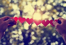 picture of hand heart  -  hands holding a string of paper hearts up to the sun during sun toned with a retro vintage instagram filter effect  - JPG