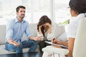 Couple fighting together in front of their therapist in the office