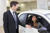 Businessman showing something to a woman at new car showroom