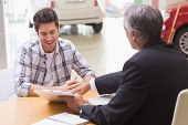 Salesman showing client where to sign the deal at new car showroom