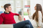 Girl photographs her boyfriend in the living room.Selective focus