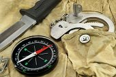 Knife, Compass And Handcuffs On The Camouflage Background