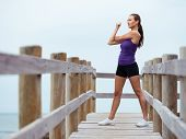 Sporty young woman stretching on the sea coast