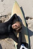 A surfer relaxing and lying on his surfboard at the beach