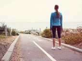 Sporty young woman standing and gettng eady for a run