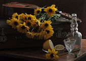 Wine-glass Of Vodka With A Lemon And A Bouquet Of Camomiles And A Mandoline On An Old Suitcase
