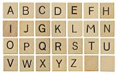 stock photo of alphabet  - Alphabet letters on wooden scrabble pieces isolated on white - JPG