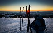 Backcountry skier taking a rest on the summit and watching beautiful sunset