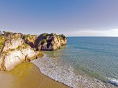 Aerial from rocks and ocean at Praia tres Irmaos in Algarve Portugal