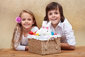 Happy kids with easter bunny and colorful eggs in a basket- shallow depth of field
